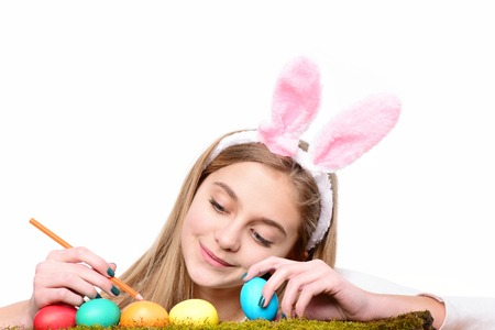 caras pintadas: happy easter girl painter in pink bunny ears with colorful painted eggs on green moss and pencil, has blond hair and smiling cute face isolated on white background. traditional spring holiday food Foto de archivo