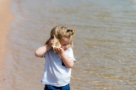 souvenir and underwater. small, little child with blond hair listening to seashell or marine shell, cute baby boy on sea beach with crystal clear water on sunny on seascape background. summer vacation
