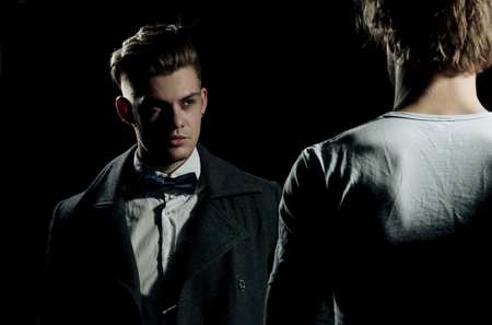 Two handsome men standing opposite on black background. Male model in white tshirt, casual wear. businessman in classic bow tie, shirt and dark coat. Fashion confrontation. Stock Photo