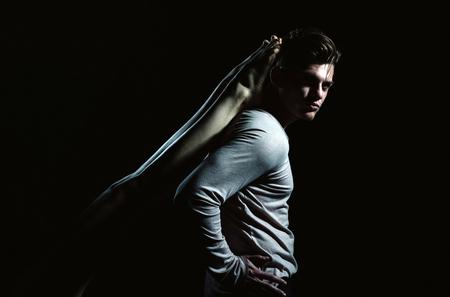 Knappe man of een jonge blanke macho met een stijlvol kapsel, haar, grijs t-shirt met lange mouwen, casual wear, poserend met sexy, vrouwelijke benen op de rug op een zwarte achtergrond Stockfoto
