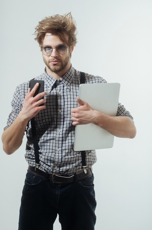 internet surfing and video conferencing, handsome man or male student, businessman, with beard and stylish, blond hair, in nerd glasses with smartphone and laptop computer. Using technology