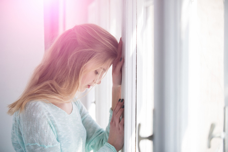 leaned: Pretty girl or young woman with blond, long hair and cute face leaned against window frame on sunny day. Future perspective and outlook