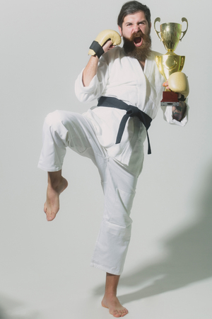 bearded karate man, long beard, brutal caucasian hipster with moustache in white kimono with black belt and boxing gloves with shouting happy face holds gold champion cup on grey background, unshaven guy Stock Photo