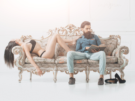 young couple of handsome bearded man in blue shirt and jeans with pretty cute girl or woman in black lingerie with sexy body on luxurious vintage couch or sofa on white background