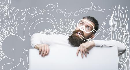 caras pintadas: hombre barbudo, barba larga, descalzo caucásico brutal con bigote en la cara sorprendida en la hoja de papel blanco con pintado bajo el agua, peces, máscara de buceo en fondo gris, espacio de la copia
