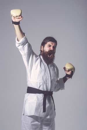 bearded karate man, long beard, brutal caucasian hipster with moustache in white kimono with black belt and boxing gloves with shouting happy face on grey background, unshaven guy