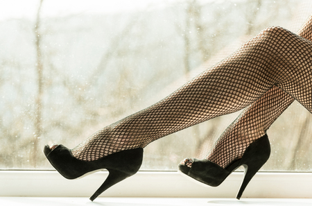 beauty and fashion, shoes with high heels on sexy, female, slim, long legs in black fishnet tights, pantyhose or stockings on white window sill on blurred natural background. Erotic and desire