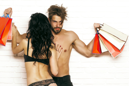 Sexy couple with shopping bags. Pretty girl or beautiful woman with buttocks, cute ass, in gstring panties kisses handsome man or muscular macho on white brick wall