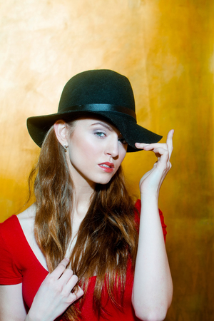 sexi: Pretty girl or beautiful fashion woman with long blond hair wearing stylish black hat and red tshirt on beige wall