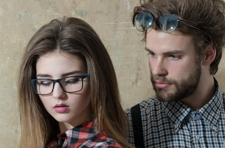 sexi: Young nerd couple of students in geek glasses. Pretty girl or beautiful woman with long hair and handsome man with beard in checkered shirts on beige background. Education and knowledge Stock Photo