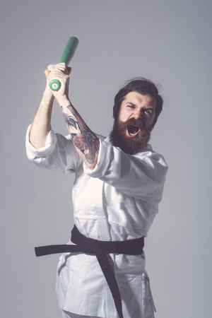 bearded karate man, long beard, brutal caucasian hipster with moustache in white kimono with black belt holds green baseball bat with shouting face on grey background, unshaven guy Stock Photo