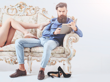 couple on couch: young couple of handsome bearded man in blue shirt and jeans with pretty cute girl or woman with sexy legs on luxurious vintage couch or sofa on white background, copy space Stock Photo