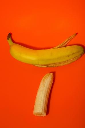 Alimentación saludable y dieta. Vitamina banana, fruta madura pelada y piel amarilla sobre fondo rojo
