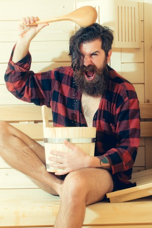 handsome bearded man or shouting guy in checkered red shirt in wooden bath holds spoon and bucket on wood background