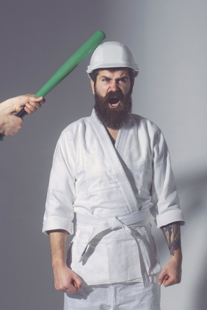 bearded karate man, long beard, brutal caucasian hipster with moustache in white kimono with black belt, builder helmet holds green baseball bat with shouting face on grey background, unshaven guy