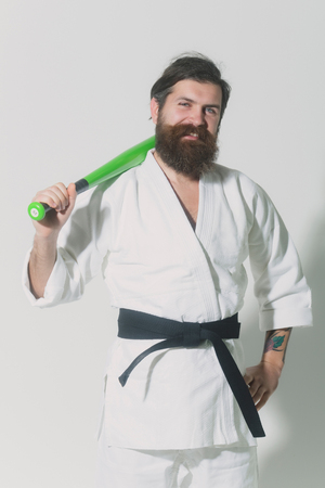bearded karate man, long beard, brutal caucasian hipster with moustache in white kimono with black belt holds green baseball bat with smiling face on grey background, unshaven guy Stock Photo