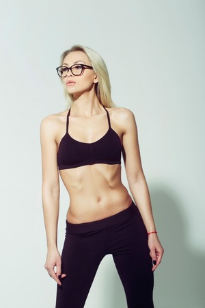 girl or sporty woman, athlete, with muscular torso in cute stylish eyeglasses, long blond hair in black sports bra, top on grey background. Fitness and healthy lifestyle Stock Photo
