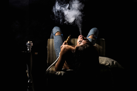 naked girl smoking hookah, pretty woman with sexy back and body in jeans sitting on eastern chair with shisha, bong or kalian as arabic tradition on black background