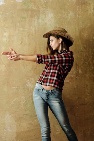 La comunicación no verbal, pistolero. bonita chica o mujer atractiva con el pelo rubio, largo en el sombrero de vaquero con estilo, camisa a cuadros roja y pantalones vaqueros azules que muestran el arma del dedo, gesto de la mano, en el fondo de la pared de color beige Foto de archivo - 76503446