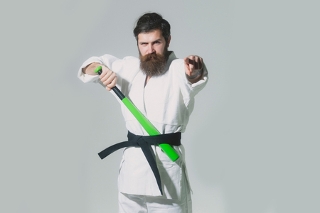 bearded karate man, long beard, brutal caucasian hipster with moustache in white kimono with black belt holds green baseball bat with serious face on grey background, unshaven guy, copy space Stock Photo