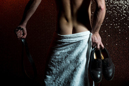 handsome muscular man or naked guy with sexy body, buttocks in white towel, holds fashionable brown male leather shoes and belt, has strong muscle on back and torso on abstract glitter background