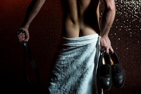 knappe gespierde man of naakt man met sexy lichaam, billen in witte handdoek, houdt modieuze bruine mannelijke lederen schoenen en riem, heeft sterke spieren op de rug en torso op abstracte glitter achtergrond