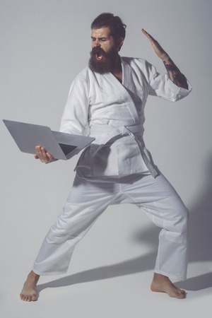 haircut: bearded karate man, long beard, brutal caucasian hipster with moustache in white kimono holds laptop with shouting face on grey background, unshaven guy