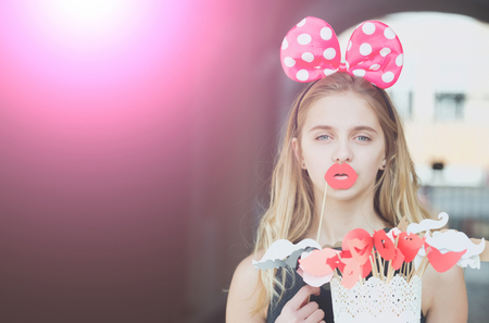 mouse: holiday celebration, funny pretty girl or young woman, teenager, with long, blond hair in cute mouse ears and red lips. Decorative props on sticks. party, birthday, anniversary. Pink light, copy space Stock Photo