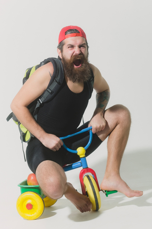 haircut: bearded man, long beard, brutal caucasian hipster with moustache in black vest, red cap with bag and apple has shouting face sitting on colorfyl bicycle toy on grey background Stock Photo