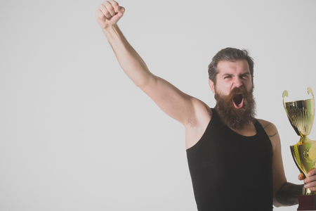 haircut: bearded man, long beard, brutal caucasian hipster with moustache in black vest holds gold champion cup with happy face on grey background, unshaven guy, copy space Stock Photo