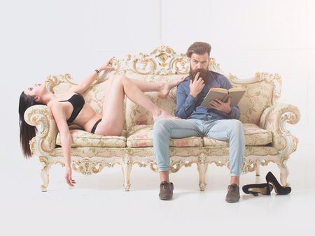 couple on couch: young couple of handsome bearded man in blue shirt and jeans with pretty cute girl or woman in black lingerie with sexy body on luxurious vintage couch or sofa on white background