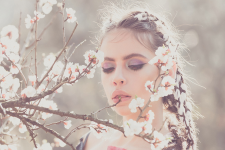 pretty girl or woman with fashionable makeup on cute face, has stylish hair, posing among blooming spring flowers or cherry blossom white color on tree branch sunny day outdoor on natural background