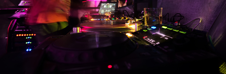 turntables for modern record and mixer with vinyl disc, professional dj equipment, in night or dance club. Colorful neon lights on dark background. Nightlife, music, entertainment
