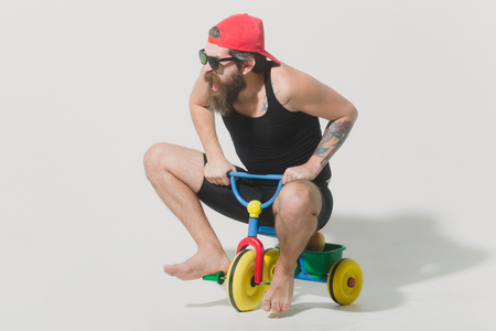 haircut: bearded man, long beard, brutal caucasian hipster with moustache in black vest and red cap, sunglasses with shouting face sitting on colorfyl bicycle toy on grey background, unshaven guy