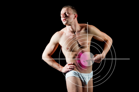 man with target on chest has bellyache standing over black background, A guy with bare body and muscular torso in white pants. Concept with Healthcare And Medicine. Stock Photo