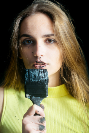 pretty woman painter or cute sexy girl builder with paintbrush, tassel or brush, building tool, painting with black color, has dirty face, long hair in yellow vest. repair, construction concept