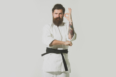 bearded karate man, long beard, brutal caucasian hipster with moustache in white kimono with black belt with serious face and ok gesture on grey background, unshaven guy, copy space