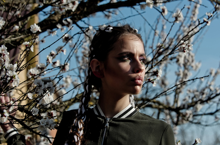 girl and flowers. pretty woman eating white cherry or apricot spring flower blooming, has fashionable makeup on face and stylish hair sunny outdoor on natural background with blue sky Zdjęcie Seryjne