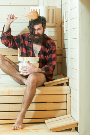 handsome bearded man or smiling guy barefoot in checkered red shirt in wooden bath holds spoon and bucket on wood background