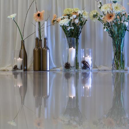 flower design in summer or spring for wedding or Valentines day, restaurant or home decoration on white glossy floor, glass bottles and vases Imagens