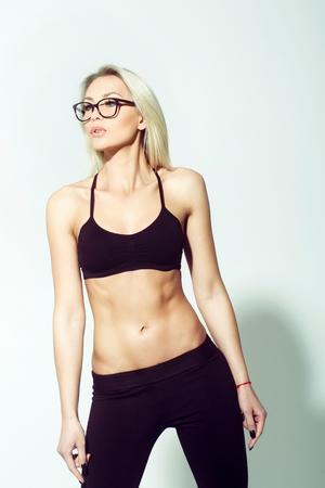 Hübsches Mädchenmodell oder moderne Frau in den netten stilvollen Brillen mit dem langen blonden Haar, das schwarzen BH, Spitze auf grauem Hintergrund trägt. Schönheit und Mode