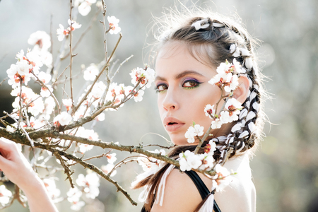woman in beautiful spring flower blossom in garden with fashion makeup on summer natural background, youth and health