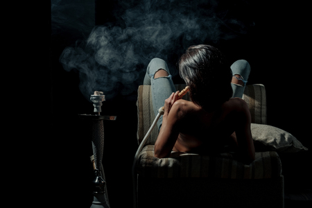pretty woman with sexy back and body in jeans sitting on eastern chair with shisha, bong or kalian as arabic tradition, naked girl smoking hookah on black background Banque d'images