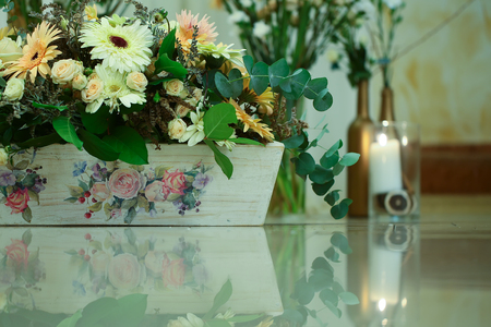Blossoming flowers and green plants in wooden flowerpot or planter with floral drawings on glossy table surface indoors on blurred background. Prosperity