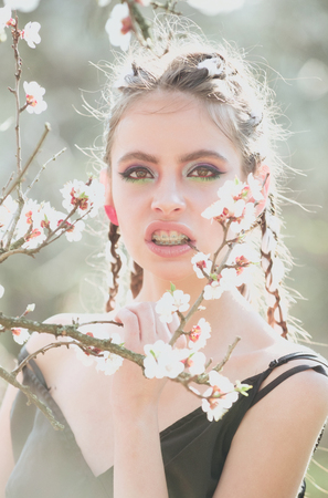 cherry tree spring blossom, beautiful girl or woman portrait in flowers, young pretty female wearing teeth braces with fashion hair, makeup in blooming park, skin care, orthodontist, dental health