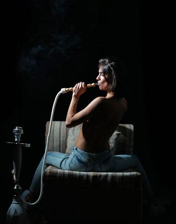 oral sex or blowjob, naked girl smoking hookah, pretty woman with sexy back and body in jeans sitting on chair with kalian as arabic tradition on black background