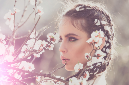 spring. pretty woman eating white cherry or apricot spring flower blooming, has fashionable makeup on face and stylish hair sunny outdoor on natural background