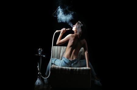 Mujer bonita atractiva que fuma pipa de agua, chica con la espalda desnuda y el cuerpo en vaqueros sentado en la silla del este con shisha, la pipa o kalian como la tradición árabe sobre fondo negro Foto de archivo - 77027543