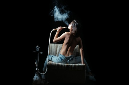 pretty sexy woman smoking hookah, girl with naked back and body in jeans sitting on eastern chair with shisha, bong or kalian as arabic tradition on black background