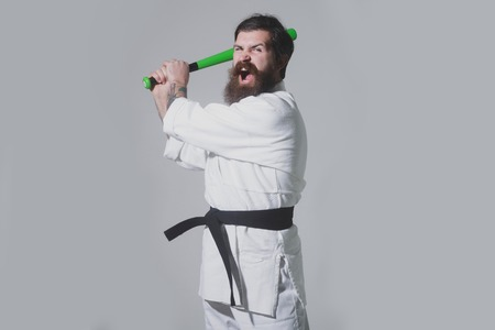 bearded karate man, long beard, brutal caucasian hipster with moustache in white kimono with black belt holds green baseball bat with shouting face on grey background, unshaven guy, copy space Stock Photo